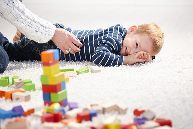Bambino gioca sul tappeto della cameretta con la mamma